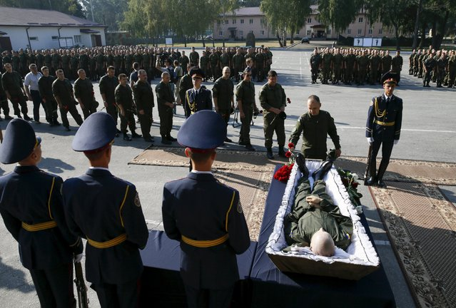 Members of Ukraine's National Guard attend a memorial service for their comrade Ihor Debrin, who was killed by a grenade during a nationalist protest outside the parliament building on Monday, outside Kiev, Ukraine, September 2, 2015. Several explosive devices, including smoke bombs and one grenade, were thrown from the crowd at the parliament during a rowdy debate on constitutional amendments that would give greater self-governance to rebel-held areas in the east. (Photo by Valentyn Ogirenko/Reuters)