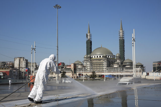 In this handout photo provided by Istanbul Mayor's office, workers clean and disinfect surfaces in the city's iconic Taksim Square amid the coronavirus outbreak, in Istanbul, Sunday, April 12, 2020. (Photo by Istanbul Mayor's Office via AP Photo)