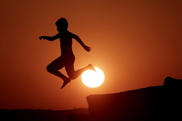 A boy jumps into the see as the sun sets during a very hot day at the suburb of Lagonissi south of Athens, Greece, 24 August 2014. A heatwave with temperatures reaching up to 40C is expected throughout Greece over the weekend before abating to more normal levels from Monday. (Photo by Yannis Kolesidis/EPA)