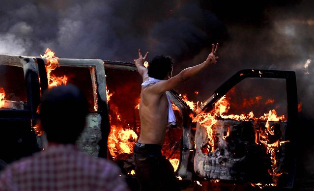 A protester flashes the victory sign next to a burning police car during clashes near the U.S. embassy in Cairo, where potesters clashed with police for the third day in a row. Egypt's Islamist President Mohammed Morsi vowed to protect foreign embassies in Cairo, where police were using tear gas to disperse protesters at the U.S. mission. (Photo by Khalil Hamra/Associated Press)