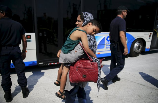 A migrant woman carries a boy as they wait to board a bus, following their arrival onboard the Eleftherios Venizelos passenger ship at the port of Piraeus, near Athens, Greece September 5, 2015. (Photo by Alkis Konstantinidis/Reuters)