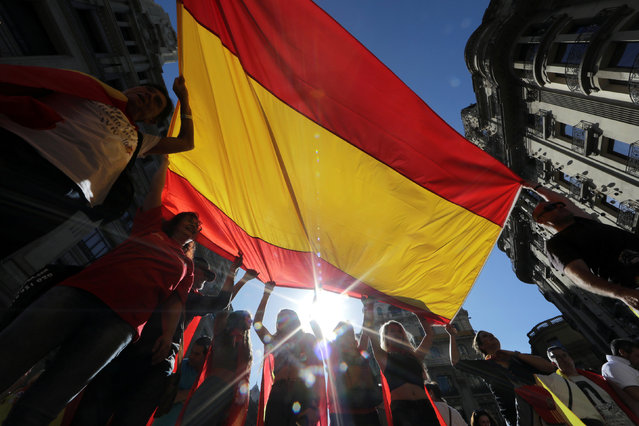 People hold a large Spanish flag during a pro-union demonstration organised by the Catalan Civil Society organisation in Barcelona, Spain October 8, 2017. (Photo by Eric Gaillard/Reuters)