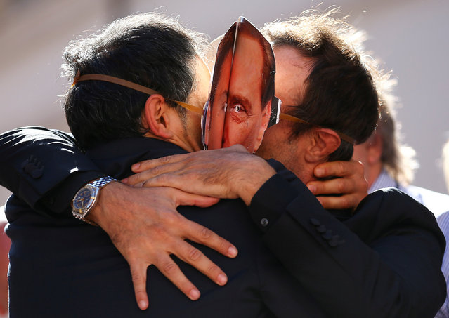 5-Star Movement supporters kiss each others as they wear masks depicting former Italian Prime Ministers Silvio Berlusconi (R) and Matteo Renzi during a protest in front of Montecitorio government palace in Rome, Italy, October 11, 2017. (Photo by Alessandro Bianchi/Reuters)