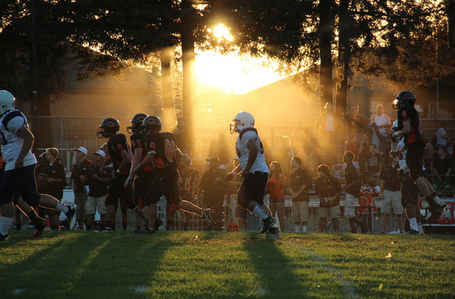 "California Football: ""As the sun sets on the Eagles home field at the California School for the Deaf in Freemont, the Richmond High Oilers try to overcome a 31 point deficit in the first half. The Oilers held a state high losing streak at 39 losses in 2005. In 2012 season, they have yet to win a game. If the past is any preview of the future, chances dwindle that they will win as the season continues. Due to academic struggles, asthma and other issues that haunt the city of Richmond, many players do not see the season to its completion"". (Photo by Lauren Kate Rosenblum/National Geographic Photo Contest"