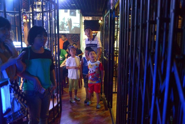 This picture taken on September 9, 2014 shows a family visiting a prison themed restaurant in Tianjin. (Photo by Wang Zhao/AFP Photo)