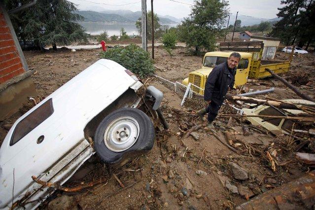 A man inspects vehicles damaged by mud due to heavy floods in Tekija village September 17, 2014. (Photo by Djordje Kojadinovic/Reuters)