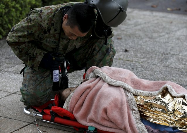 A woman talks with a Japan Self-Defense Force (JSDF) member after being rescued by a helicopter from an area flooded by the Kinugawa river, caused by typhoon Etau, upon their arrival at Ishige Sports Park acting as an evacuation center in Joso, Ibaraki prefecture, Japan, September 10, 2015. (Photo by Issei Kato/Reuters)