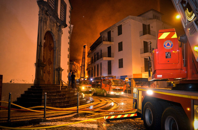 Firefighting vehicles line the street in the historical center of Funchal in Madeira island on August 9, 2016. Three people were killed and 1,000 forced to flee their homes overnight as forest fires engulfed the Portuguese island of Madeira, authorities said, as flames menaced the capital Funchal. (Photo by Helder Santos/AFP Photo)