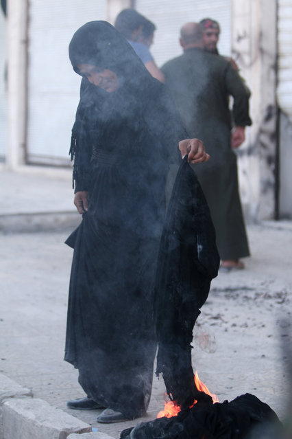 A woman sets fire to a niqab after she was evacuated with others by the Syria Democratic Forces (SDF) fighters from an Islamic State-controlled neighbourhood of Manbij, in Aleppo Governorate, Syria, August 12, 2016. (Photo by Rodi Said/Reuters)