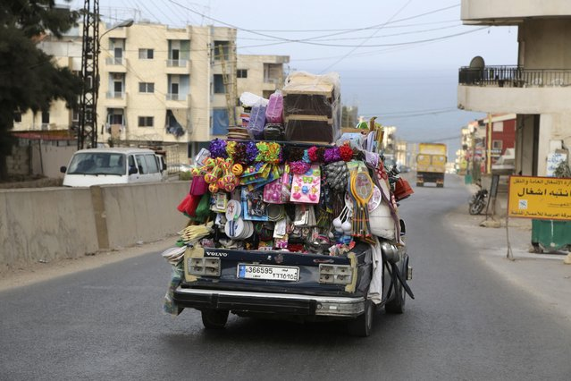 A vendor drives in a vehicle with various items on sale in Beirut September 25, 2014. (Photo by Sharif Karim/Reuters)
