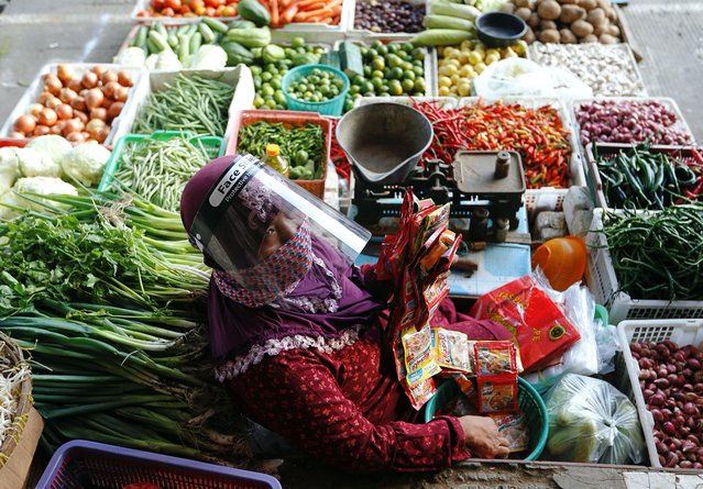 A vendor wearing a face shield and a protective face mask sells vegetables at a traditional market as the government eases restrictions in Jakarta, Indonesia on June 16, 2020. (Photo by Ajeng Dinar Ulfiana/Reuters)