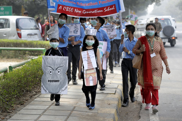 School children hold banners take out march to express their distress on the alarming levels of pollution in the city, in New Delhi, India, Wednesday, November 15, 2017. Thick smog has constricted India's capital this week, smudging landmarks from view and leaving residents frustrated at the lack of meaningful action by authorities. The air was the worst it has been all year in New Delhi, with microscopic particles that can affect breathing and health spiking to 75 times the level considered safe by the World Health Organization. (Photo by Manish Swarup/AP Photo)