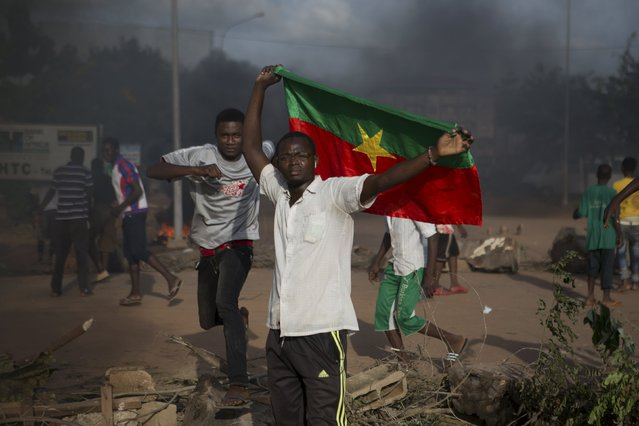 An anti-coup protester holds a Burkinabe flag in Ouagadougou, Burkina Faso, September 18, 2015. (Photo by Joe Penney/Reuters)