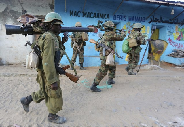 Somalia's army soldiers and peacekeepers from the African Union Mission in Somalia (AMISOM) enter the town of Barawe during the second phase of Operation Indian Ocean October 6, 2014. Somalia's army and African troops deployed forces on Monday inside the strategic port which they retook from Islamist rebels at the weekend, promising residents they would be protected. (Photo by Feisal Omar/Reuters)