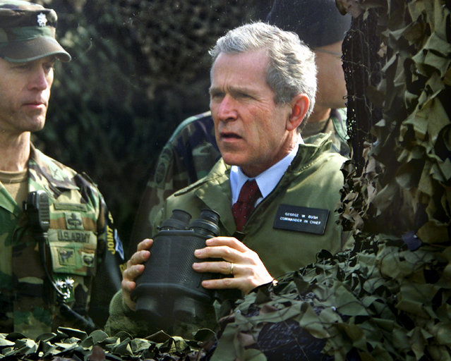 In this February 20, 2002 file photo, U.S. President George W. Bush looks out at North Korea at Observation Point Ouellette in the Demilitarized Zone (DMZ), the tense military border between the two Koreas, in Panmunjom, South Korea. Straddling the world's most heavily fortified border, the Korean truce village of Panmunjom is a potentially dangerous flashpoint where North Korean soldiers hacked to death two American soldiers at the height of the Cold War. It's also where the rival Koreas have held rare high-profile talks, and top American officials have visited to demonstrate American commitment to defending South Korea. (Photo by J. Scott Applewhite/AP Photo)