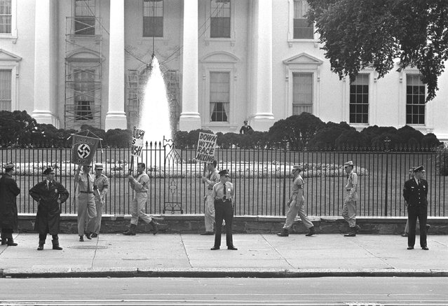 Uniformed American Nazis wearing Swastika armbands carry racist placards in a march along Pennsylvania Ave., in front of the White House in Washington, D.C., September 23, 1962. Police keep watch nearby. (Photo by AP Photo)