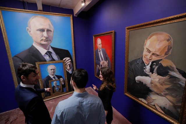 """People look at the paintings depicting Russian president Vladimir Putin at the """"SUPERPUTIN"""" exhibition at UMAM museum in Moscow, Russia on December 6, 2017. (Photo by Maxim Shemetov/Reuters)"""