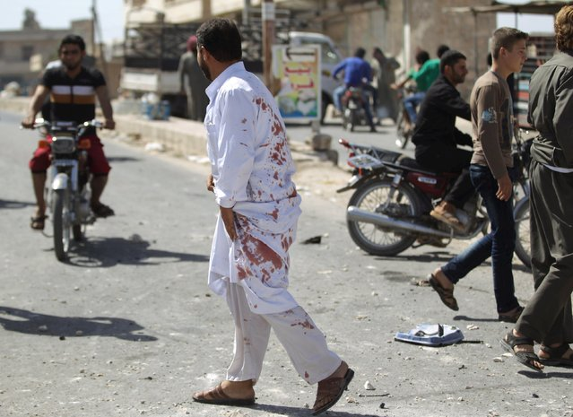 A man, in clothes stained with blood, walks at a site hit by what activists said was an airstrike by forces loyal to Syria's President Bashar al-Assad, in Kafruma village in the southern countryside of Idlib, Syria September 24, 2015. An internet cafe was was hit during the airstrike, killing several children, activists said. (Photo by Khalil Ashawi/Reuters)