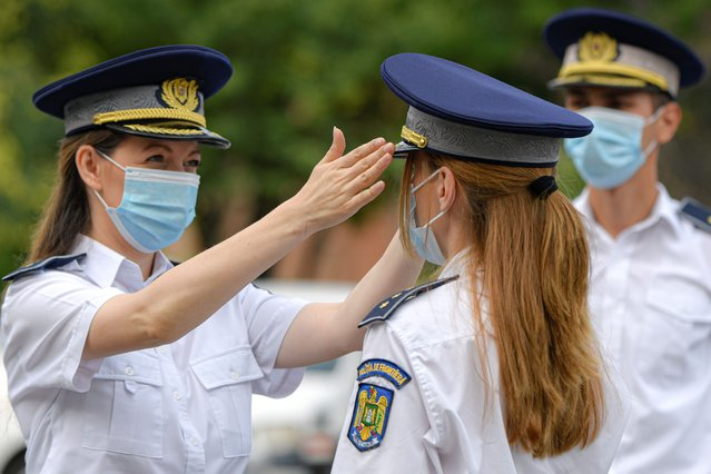 Border guard officers, wearing masks against COVID-19 infection adjust their outfits before a distinguished service awards ceremony for employees of the interior ministry in Bucharest, Romania, Thursday, July 16, 2020. Romania has registered on Thursday the highest number of COVID-19 infection cases since the pandemic reached the country in February, 777 in a 24 hours interval, as many fail to observe the mandatory protection measures, like the use of a face mask indoors or maintaining social distancing. (Photo by Andreea Alexandru/AP Photo)