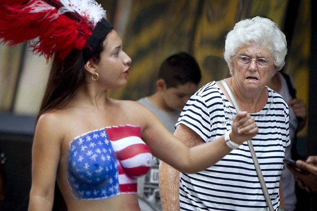 A woman walks past a woman who poses for tips wearing body paint and underwear in Times Square in New York in this August 18, 2015 file photo. (Photo by Carlo Allegri/Reuters)