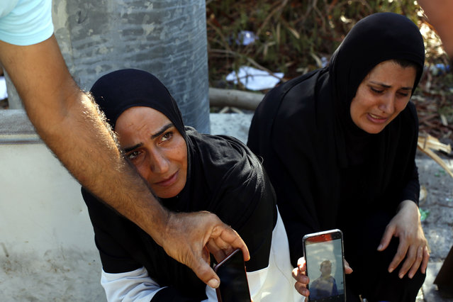 Zeinab Zer Eldin, left, and her sister-in-law shows a photo of her missing husband near the site of the explosion in the port of Beirut, Lebanon, Friday, August 7, 2020. Rescue teams were still searching the rubble of Beirut's port for bodies on Friday, nearly three days after a massive explosion sent a wave of destruction through Lebanon's capital, killing over a hundred people and wounding thousands. (Photo by Thibault Camus/AP Photo)