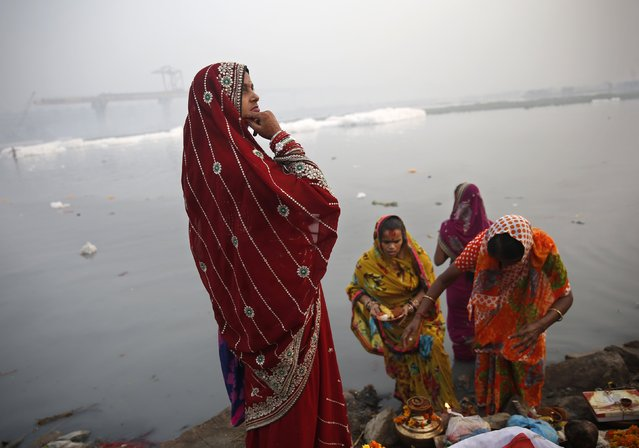 Hindu women worship the Sun god Surya on the banks of the river Yamuna during the Hindu religious festival of Chatt Puja in New Delhi October 30, 2014. (Photo by Ahmad Masood/Reuters)