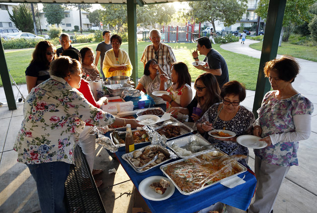 Retired professor Carlos Jainga, 71 (6th R) and his wife Estrella Jainga, 68, (L) attend a farewell party for their friend Dolores Saballo, 65, (R) who is returning to the Philippines, at a park in Torrance, California September 30, 2014. The Jaingas emigrated to the U.S. from the Philippines in 2005, following their eldest son, and became U.S. citizens earlier this month. (Photo by Lucy Nicholson/Reuters)