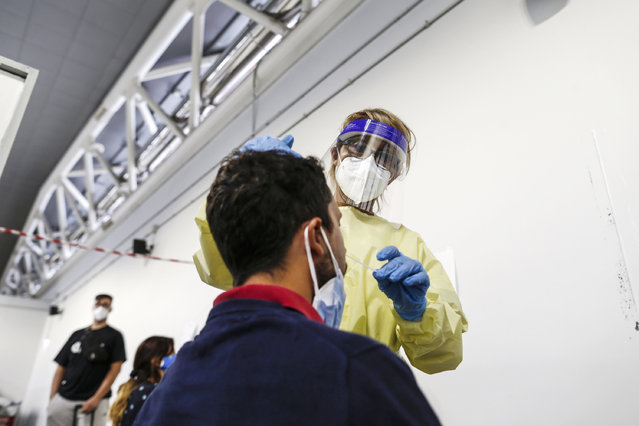 A passenger arriving in Rome from one four Mediterranean at Rome's Ciampino airport is tested for COVID-19, Tuesday, August18, 2020. Italy's health minister issued an ordinance requiring the tests for all travelers arriving in Italy from Croatia, Greece, Malta or Spain. (Photo by Cecilia Fabiano/LaPresse via AP Photo)