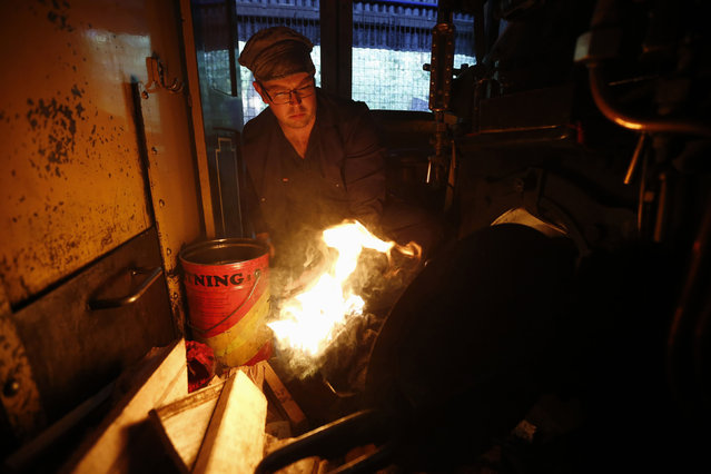 Puffing Billy trainee fireman Winston Martin lights a fire to put into the firebox of a steam locomotive, part of the four-hour-long process to prepare the engine, at Belgrave near Melbourne, October 20, 2014. (Photo by Jason Reed/Reuters)