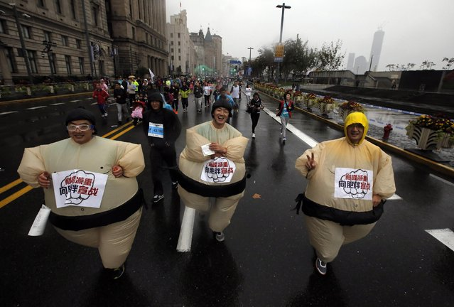 Participants wear costumes while competing in the Shanghai International Marathon November 2, 2014. (Photo by Carlos Barria/Reuters)