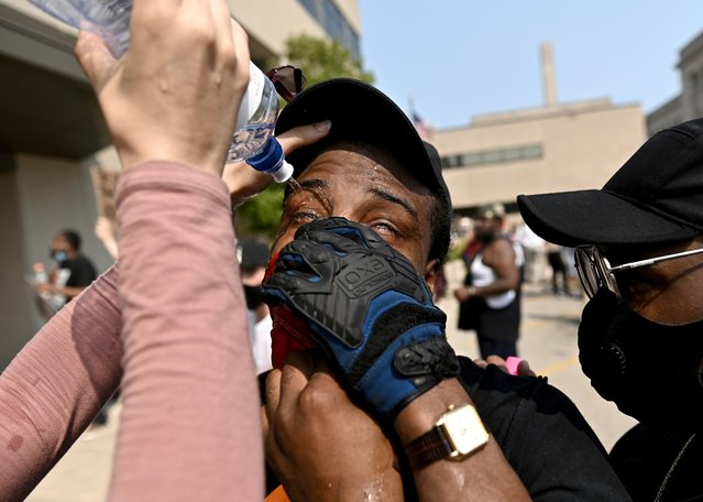 A man has his eyes flushed after being pepper sprayed by police as protestors rallied outside the Kenosha County Public Safety Building after a Black man, identified as Jacob Blake, was shot several times by police last night in Kenosha, Wisconsin, U.S. August 24, 2020. (Photo by Stephen Maturen/Reuters)