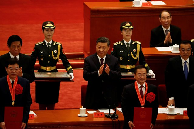 Chinese President Xi Jinping applauds as people receive recognitions during a meeting to commend role models in China's fight against the coronavirus disease (COVID-19) outbreak, at the Great Hall of the People in Beijing, China on September 8, 2020. (Photo by Carlos Garcia Rawlins/Reuters)