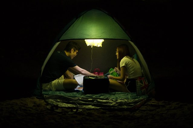 A couple picnic in a tent during mid-Autumn Festival celebrations on Shek O beach in Hong Kong, China, 16 September 2016. The festival is celebrated by ethnic Chinese, Koreans and Vietnamese people. It is also known as the Moon Festival or Moon Cake Festival. (Photo by Jerome Favre/EPA)