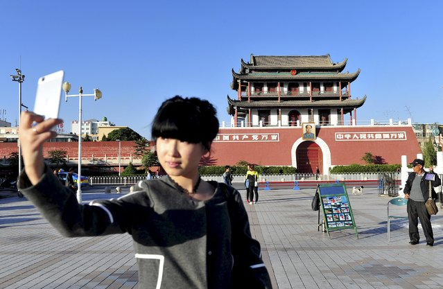 """A woman poses for a selfie in front of the Nanxun Gate, also known as the """"small Tiananmen Gate"""", in Yinchuan, Ningxia Hui Autonomous Region, China, October 9, 2015. The 27.5-metre-high gate is the only remaining gate of ancient Yinchuan's city wall. The gate's appearance today resembles Beijing's Tiananmen Gate, after it was renovated in the 1950s. Since then, the gate and the South Gate Square nearby became a venue for major celebration events, local media reported. (Photo by Reuters/Stringer)"""