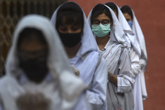 Students wearing facemasks take part in an assembly at a school in Karachi on September 15, 2020 after the educational institutes were reopened nearly six months after the spread of the Covid-19 coronavirus. (Photo by Asif Hassan/AFP Photo)