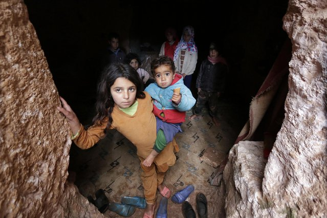 Mariam, a 9-year-old girl, carries her brother as she stands with other children at an underground ancient cemetery in Jabal al-Zawiya in the southern countryside of Idlib November 26, 2014. (Photo by Khalil Ashawi/Reuters)