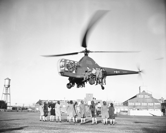 An Army Sikorsky R-5 helicopter, undergoing record trials, demonstrates its lifting power by carrying 17 persons and pilot aloft as female onlookers wave in Bridgeport, Conn., January 10, 1946. During the tests records were claimed for altitude speed and both altitude and speed with payload. (Photo by Anthony Camerano/AP Photo)