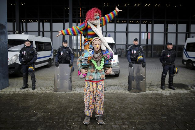 """French riot police stand guard as people dressed as clowns attend a protest demonstration against """"police brutality"""" in Nantes, western France, November 22, 2014. People protest against the use of force by police and in memory of 21-year-old environmentalist Remi Fraisse who died during a violent stand-off over the weekend October 25-26 between police and ecology protesters seeking to prevent construction of a dam in Sivens. (Photo by Stephane Mahe/Reuters)"""