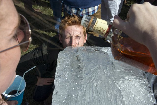 A man drinks alcohol from the bottom of an ice luge while a woman pours the liquor at the Far Hills Race Day at Moorland Farms in Far Hills, New Jersey, October 17, 2015. (Photo by Stephanie Keith/Reuters)