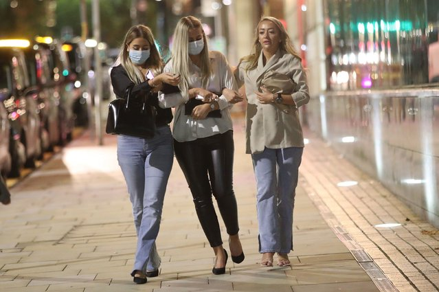 Three women out for the evening in Manchester on October 11, 2020, ahead of a possible government announcement on Monday. Cities in northern England and other areas suffering a surge in Covid-19 cases may have pubs and restaurants temporarily closed to combat the spread of the virus. (Photo by Danny Lawson/PA Images via Getty Images)