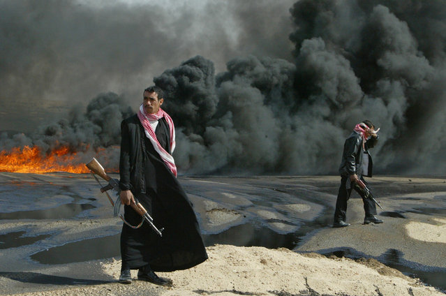 Iraqi policemen guard a sabotaged burning pipeline near the city of Kerbala, on February 23, 2004. (Photo by Faleh Kheiber/Reuters/The Atlantic)