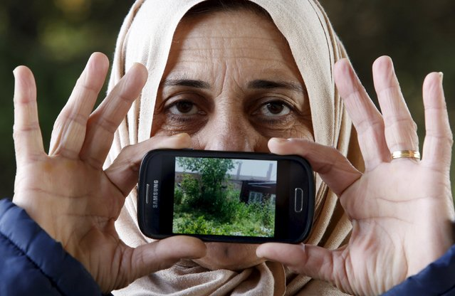 Migrant Logine from Hamslo, Syria, shows a picture of her home as she waits to cross the Slovenia-Austria border in Sentilj, Slovenia October 25, 2015. (Photo by Srdjan Zivulovic/Reuters)