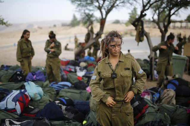 An Israeli soldier of the Caracal battalion stands next to backpacks after finishing a 20-kilometre (12-mile) march in Israel's Negev desert, near Kibbutz Sde Boker, marking the end of their training, in this May 29, 2014 file photo. (Photo by Amir Cohen/Reuters)