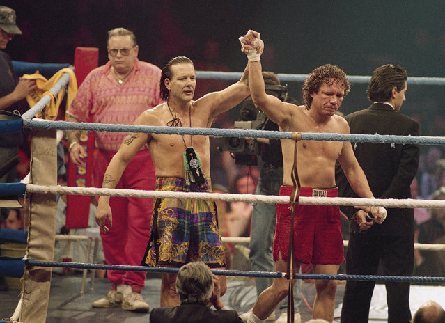U.S. actor-boxer Mickey Rourke (L) raises arms with Canadian boxer Terry Jessmer after their 4-round boxing bout in Oviedo northern Spain, December 12, 1992. Rourke won the decision in a bout in which both fighters were constantly jeered for their poor boxing skills. (Photo by Denis Doye/AP Photo)