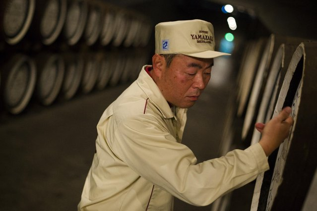 Senior General Manager of Suntory Holdings' Yamazaki Distillery Takahisa Fujii knocks on whisky casks to check its levels in the distillery's storage in Shimamoto town, Osaka prefecture, near Kyoto, December 1, 2014. (Photo by Thomas Peter/Reuters)