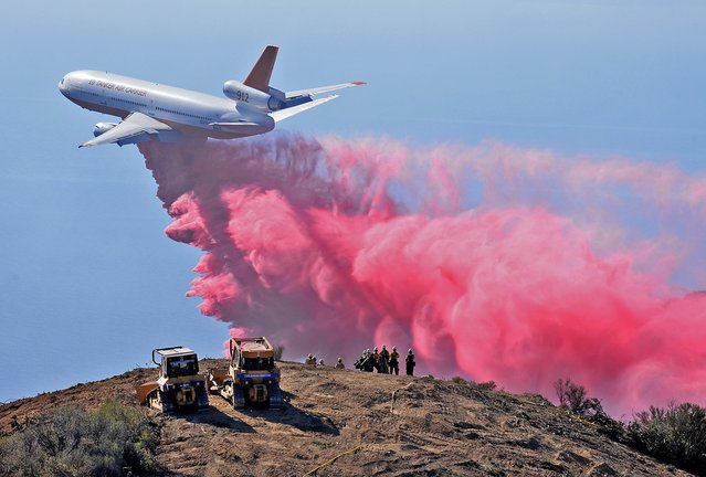 A DC-10 air tanker drops phos-check on the Gibraltar Fire as firefighters watch from a peak in the Los Padres National Forest above Santa Barbara, California in this handout photo from the Santa Barbara County Fire Department released to Reuters October 29, 2015. The fire burned about 50 acres but had firefighters on high alert as hot, dry Santa Ana winds have returned to southern California. (Photo by Mike Eliason/Reuters/Santa Barbara County Fire Department)