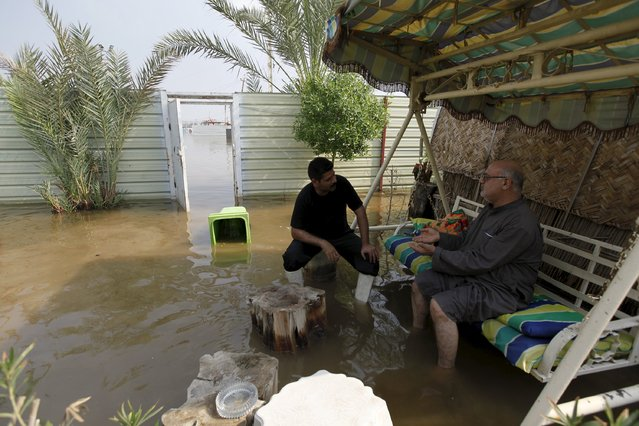 Men chat at a flooded house after heavy rainfall in Baghdad, Iraq, October 31 2015. (Photo by Ahmed Saad/Reuters)