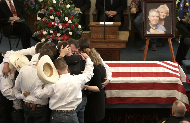 The family of Kaufman County District Attorney Mike McLelland and his wife, Cynthia, comfort each other during their funeral services at  the First Baptist Church of Wortham Friday, April 5, 2013, in Wortham, Texas.  The couple was found shot to death Saturday in their house near Forney, about 20 miles east of Dallas. No arrests have been made. (Photo by L. M. Otero/AP Photo)