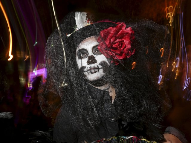 "A reveler dressed in a ""Dia de Muertos"" or ""Day of the Dead"" theme poses for a photo while taking part in the Greenwich Village Halloween Parade in the Manhattan borough of New York, October 31, 2015. (Photo by Carlo Allegri/Reuters)"