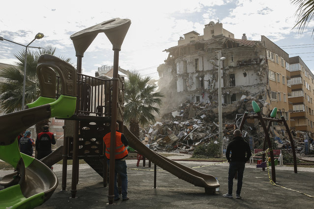 People watch from a playground the debris of a collapsed building, in the coastal city of Izmir, Turkey, Monday, November 2, 2020. In scenes that captured Turkey's emotional roller-coaster after a deadly earthquake, rescue workers dug two girls out alive Monday from the rubble of collapsed apartment buildings three days after the region was jolted by quake that killed scores of people. Close to a thousand people were injured. (Photo by Emrah Gurel/AP Photo)